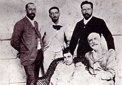 Francisco Giner de los Ríos (sentado a la derecha) con su nuera y nieto, y, arriba, a la derecha, su hijo Alberto, acompañados de los señores Rubio y Cossio, miembros de la institución.