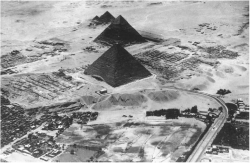 Fig. 79. Aerial view of the Giza plateau, with the Great Pyramid of Khufu in the foreground and the pyramids of Khafre and Menkaure behind, looking southwest. The mastaba tombs of the Eastern and Western Cemeteries are visible on either side of the Great Pyramid, and the Great Sphinx appears at the center left edge of the image.