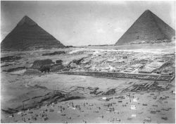 Fig. 87. General view of the Giza necropolis, showing (far to near) the pyramids of Khufu (right) and Khafre (left), the Central Field mastabas excavated by Selim Hassan, the pyramid tomb of Queen Khent-kawes, the causeway and mud-brick houses from the Fifth and Sixth Dynasties, the valley temple of Menkaure, and a modern cemetery in the foreground, looking northwest, August 22, 1937