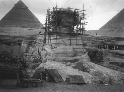 Fig. 90. The Great Sphinx, with the restoration scaffolding of Emile Baraize, looking northwest, December 26, 1925. The pyramids of Khufu (right) and Khafre (left) are in the background
