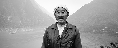 Daxi, Fengjie County, 2001. Cheng Ke Hua stands on the path in front of his family home in the village of Daxi at the junction of Fengjie and Wushan counties. Behind is the entrance to Qutang Gorge. The water will eventually rise to the level at which he stands.