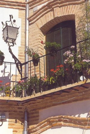 Detalle de la espectacular Plaza Mayor de Archidona, en la que se armoniza el blanco de los muros con el rojizo del ladrillo y la forja de balcones y farolas.