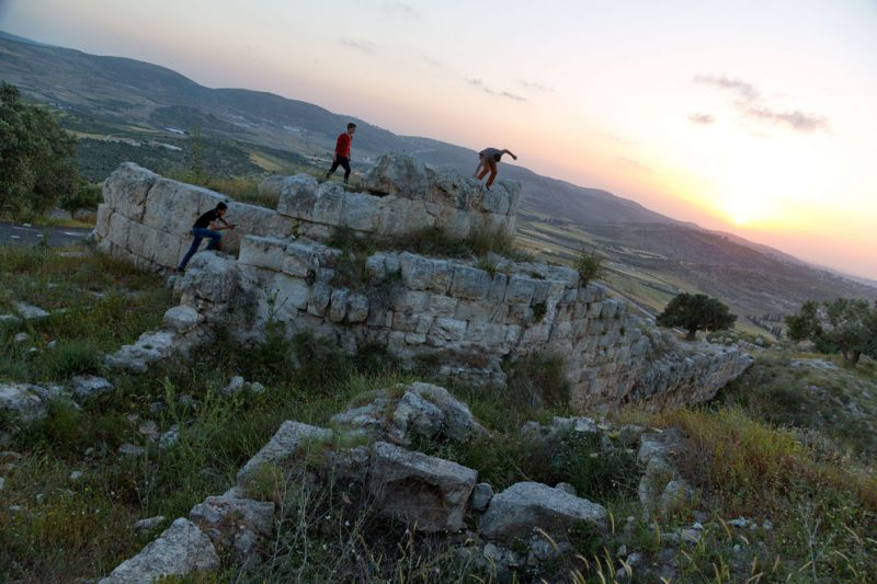 In the West Bank, youths explore Roman ruins at Samaria-Sebaste, a site divided between Israeli and Palestinian control.