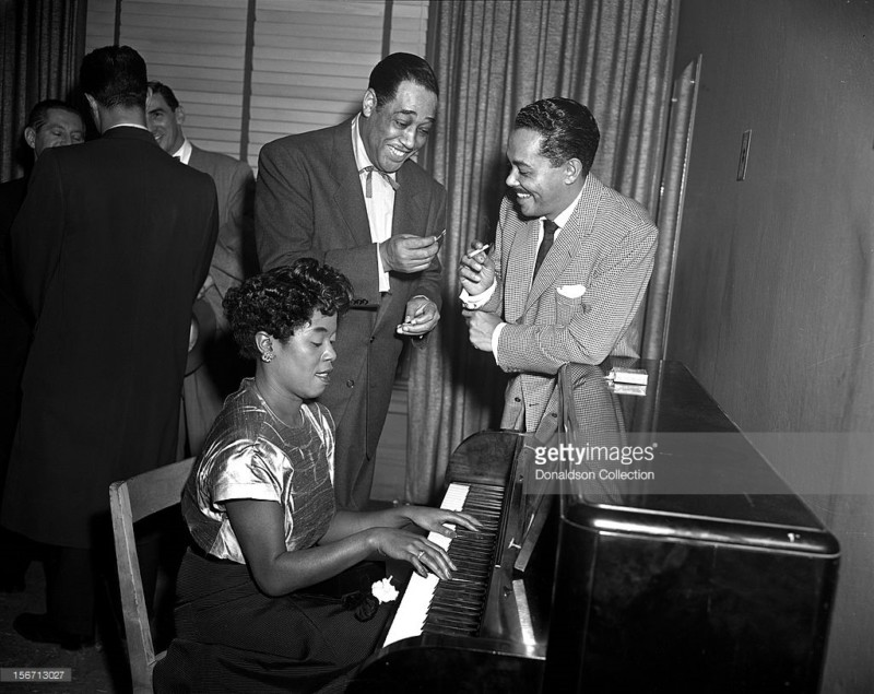 Jazz Singer Sarah Vaughan plays piano as bandleader Duke Ellington and singer Billy Eckstine share a joke backstage at Carnegie Hall on December 1, 1951 in New York City, New York.