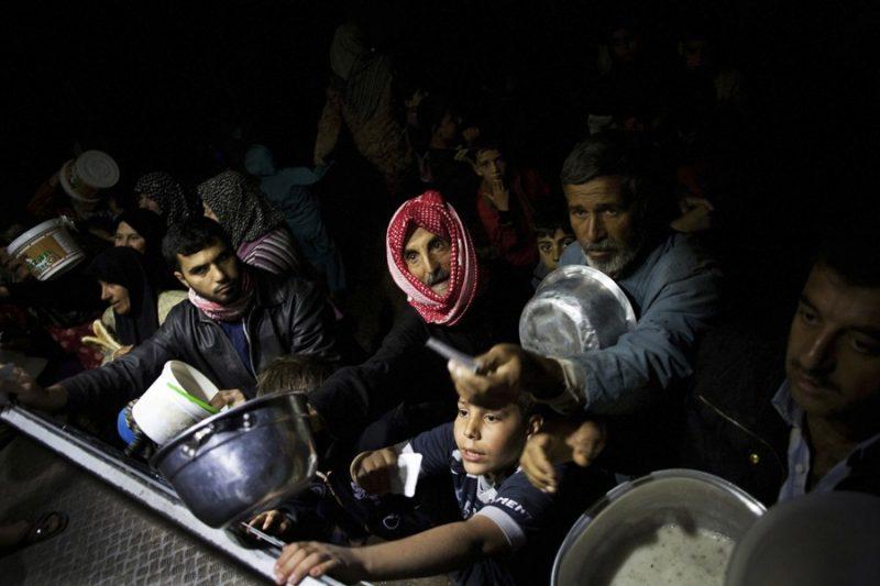 Refugiados sirios esperan comida en una cocina benéfica de una ONG en un campamento cerca de Azaz, Siria (23 de octubre de 2012). Foto de Manu Brabo, Associated Press.