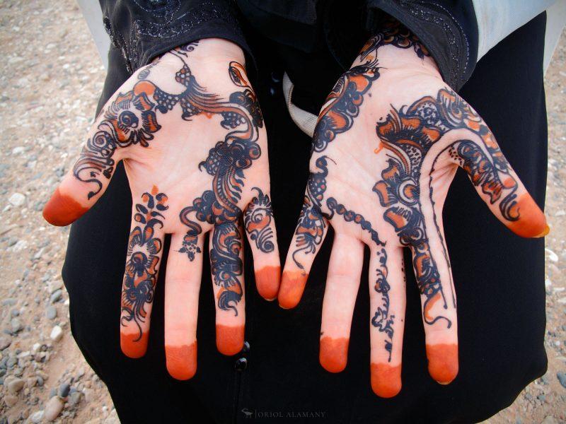 Una mujer muestra sus manos decoradas con alheña en Socotra. Este tinte natural de color rojizo, fabricado con las hojas secas del arbusto homónimo, es parte importante de la cultura de esta isla del Índico. Las mujeres lo utilizan sobre todo en ocasiones especiales para decorar sus manos, pies y antebrazos (Fotografía: Oriol Alamany)