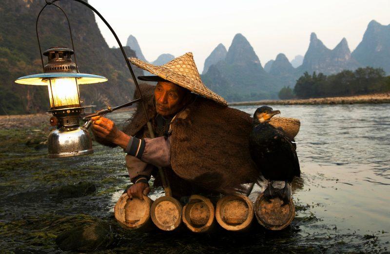 Un pescador enciende su lámpara de parafina lista para una noche de pesca en el río Li con sus cormoranes