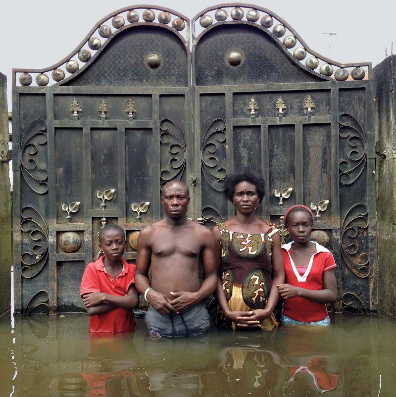 Joseph y Endurance Edem, con su hijo Godfreedom y su hija Josephine, posan delante del portalón de su casa de Igbogene, en Nigeria. En 2012 este país africano sufrió las peores inundaciones que se han registrado en medio siglo.