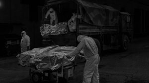 Trabajadores de Novara (Italia) llevan los féretros desde el camión militar hasta el crematorio.