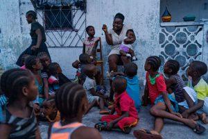 Los niños se reúnen alrededor de Patience Brooks, que sostiene a su hija menor, Marta, en su regazo en Mamba Point, Monrovia