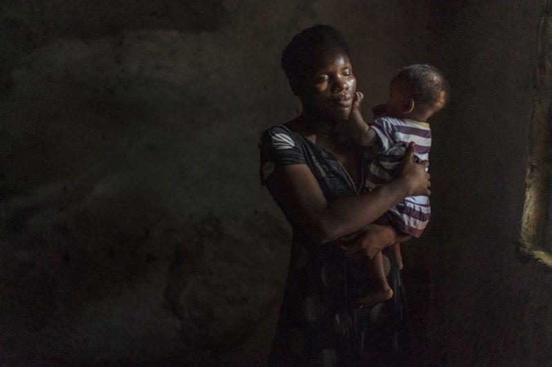 Después de muchos años sin hogar, Christiana Gmah canta canciones a su hija Orinna en su casa en West Point (Monrovia). Sus padres la echaron cuando quedó embarazada a los 13 años de su primera hija, Georgina. Hoy vende té y pan por la noche para mantener a sus hijas.