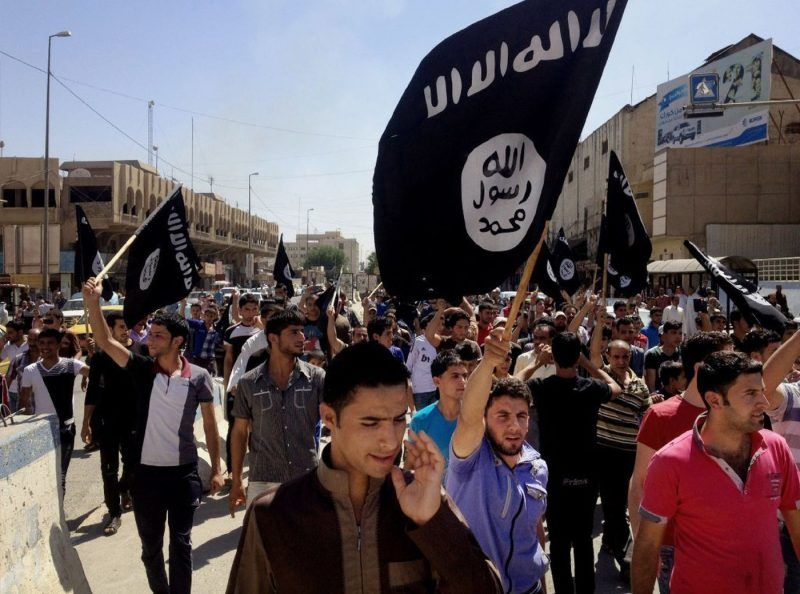 Pro-ISIS demonstrators are seen on Monday chanting slogans in front of the provincial government headquarters in Mosul, Iraq. (Associated Press)