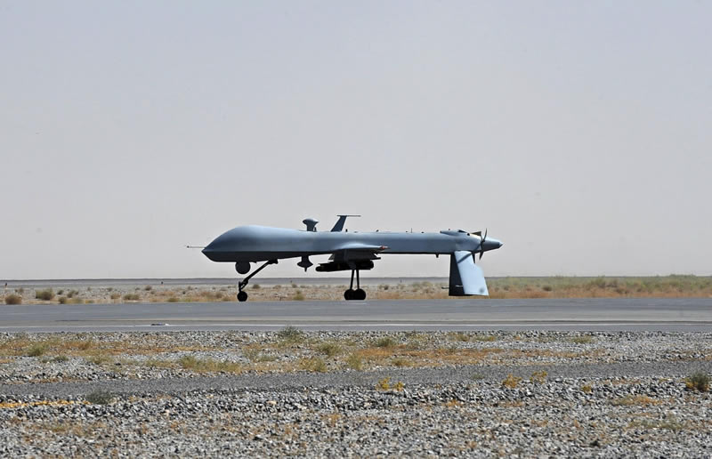 FILE - In this June 13, 2010, file photo a U.S. Predator unmanned drone armed with a missile stands on the tarmac of Kandahar military airport in Afghanistan. (MASSOUD HOSSAINI/AP)