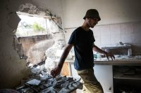 An Israeli soldier inspects an Israeli home allegedly hit by a Hamas rocket in Sderot, Israel. (Andrew Burton / Getty Images)