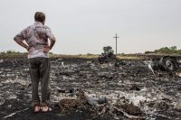 A man examined debris on Friday from the Malaysia Airlines crash a day earlier, in a field in Grabovo, Ukraine. Credit Brendan Hoffman/Getty Images