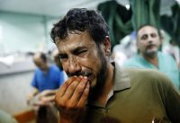 A Palestinian man cries after bringing a child, wounded during fighting between Israeli forces and Hamas militants, to the emergency room room. (Lefteris Pitarakis / AP)