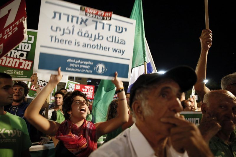 Demonstrators hold up anti-war banners as thousands of Israelis protest during a left-wing peace rally in the coastal city of Tel Aviv calling for the Israeli government to negotiate with the Palestinian Authority on August 16, 2014. Israeli and Palestinian negotiators are poised to resume indirect talks with Egyptian mediators on reaching a more permanent ceasefire before a current truce expires at midnight on August 18. (Gali Tibbon/AFP/Getty Images)