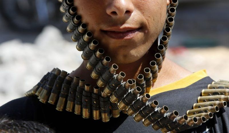 A Palestinian youth wraps a bandolier of spent bullets leftover by the Israeli army, next to his destroyed home in Beit Hanoun, Gaza Strip, Monday, Aug. 11, 2014. (AP Photo/Hatem Moussa)