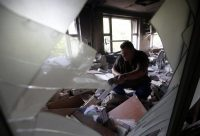 A man inspects wreckage inside a damaged building following what locals say was shelling by Ukrainian forces in Donetsk August 7, 2014. The Ukrainian government said on Thursday it was suspending a ceasefire with separatist rebels at the crash site of the Malaysian airliner after an international recovery mission had been halted. (Sergei Karpukhin/Reuters)