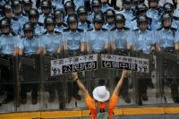 """A defiant protester waving placards that read """"Occupy Central"""" and """"Civil Disobedience'' as riot police formed a phalanx outside government headquarters in Hong Kong on Saturday. Credit Vincent Yu/Associated Press"""