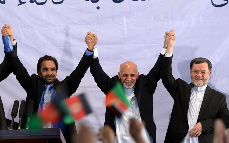 Afghan President-elect Ashraf Ghani Ahmadzai, center, holds hands with his supporters as they gesture to the crowd during a gathering in Kabul on Monday. (Wakil Kohsar / AFP/Getty Images)