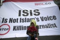 An Indonesian journalist holds flowers as she sits in front of a banner during a protest in Jakarta against the killing of journalists by Islamic State. (Mast Irham / EPA)