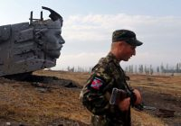 A pro-Russian separatist standing near a damaged war memorial on a hill east of Donetsk. Credit Maxim Shemetov/Reuters