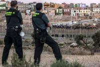 Spanish Guardia Civil watch as would-be immigrants from Africa sit atop a fence after scrambling over two other border barriers on Spain's tiny north African territory of Melilla. (Jose Colon / AFP/Getty Images)