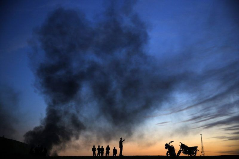 Kurdish refugees near Turkey's border with Syria on Oct. 26, as smoke rises over Kobani in the distance. Credit Yannis Behrakis/Reuters