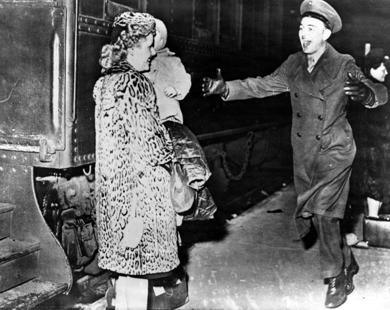 A U.S. Marine greets his British war bride carrying his son after their arrival in the U.S. following the end of World War II. (Keystone / Getty Images)