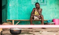 A boy under quarantine sits behind a cordon outside his house in Moyamba town on the outskirts of Freetown, Sierra Leone. Photograph: Michael Duff/AP