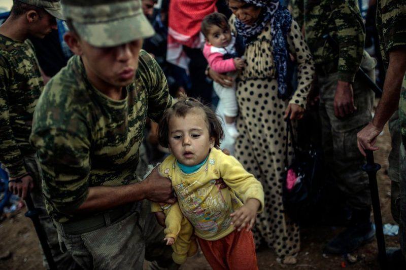Turkish soldiers helping Kurdish families fleeing the fighting in Syria. Credit Bulent Kilic/Associated Press
