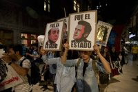"In Mexico City, demonstrators march with signs saying ""It was the state"" and showing images of Mexican President Enrique Peña Nieto, right, and Atty. Gen. Jesus Murillo Karam in a protest over the disappearance of 43 college students. (Eduardo Verdugo / Associated Press)"