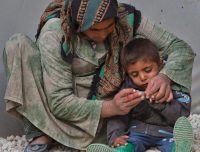 A Syrian Kurdish refugee man from the Kobani area trims the nails of a child at a camp in Suruc, on the Turkey-Syria border, Thursday, Nov. 20, 2014. (Vadim Ghirda/AP)