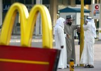 Three Arab taxi drivers chat near a McDonald's restaurant in Kuwait City November 10, 2002. REUTERS/Chris Helgren