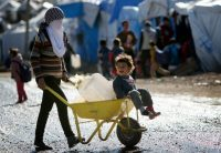 A Syrian-Kurdish refugee carries water containers at a camp in the Kurdish region of northern Iraq. Photograph: Safin Hamed/AFP/Getty Images