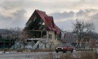 A car drives by a private house destroyed in a recent battles between the Ukrainian army and pro-Russian separatists in Semenivka, Donetsk region, eastern Ukraine, Monday, Dec. 29, 2014. (Efrem Lukatsky/AP)