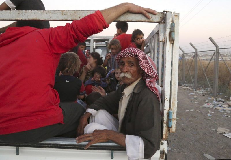 Displaced Iraqis from the Yazidi community arrive to the camp of Bajid Kandala at Feeshkhabour town near the Syria-Iraq border, in Iraq Saturday, Aug. 9, 2014. (Khalid Mohammed/AP)