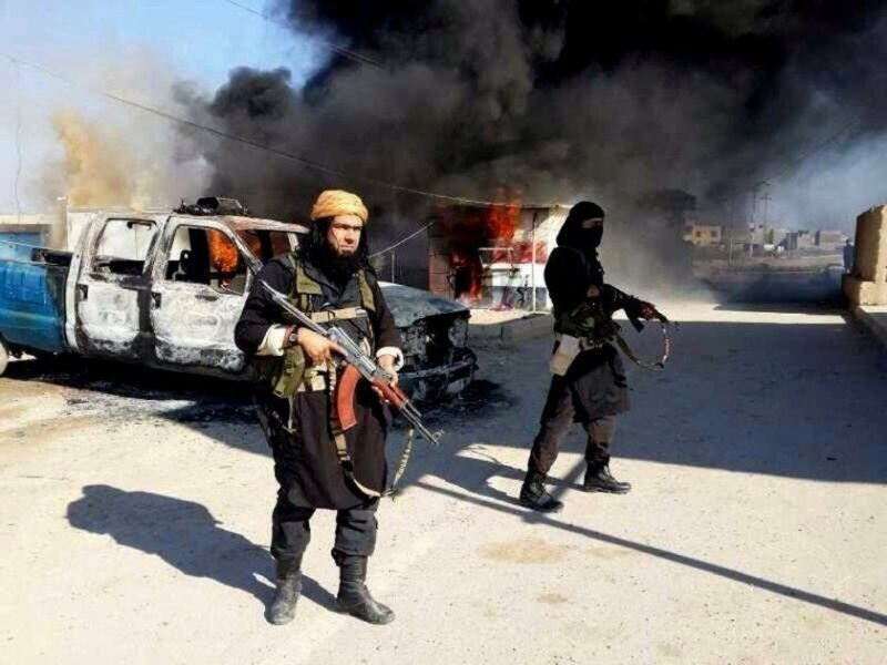 An estimated 3,400 foreign fighters for Islamic State have come from Western countries. Above, Islamic State fighters stand next to a burning vehicle in Iraq. (Associated Press)