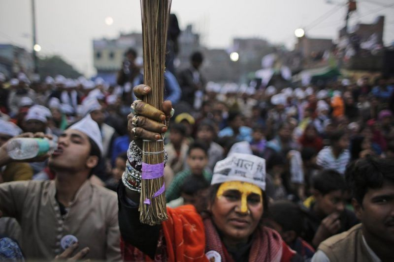A supporter of the Aam Aadmi Party, or Common Man Party, holds up a broom, the party symbol, at an election rally on Feb. 3. Credit Altaf Qadri/Associated Press