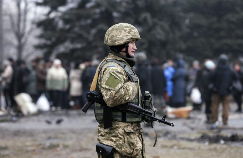A Ukrainian serviceman patrols the area as people stand in line to receive humanitarian aid near a delivery point in the government forces-controlled town of Debaltseve, Donetsk region, Feb. 6, 2015. REUTERS/Maxim