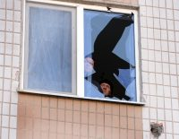 Two men look at a broken window in an appartment in Donetsk, on February 12, 2015. (Vasily Maximov/AFP/Getty Images)