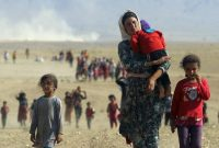 Displaced people from the minority Yazidi sect, fleeing violence from forces loyal to the Islamic State in Sinjar town, walk toward the Syrian border, Aug 11, 2014. REUTERS/Rodi Said/Files