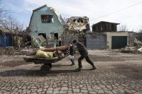 A man pushes a wheelbarrow past a house damaged by fighting in the town of Debaltseve, Ukraine, Feb. 25, 2015. REUTERS/Baz Ratner