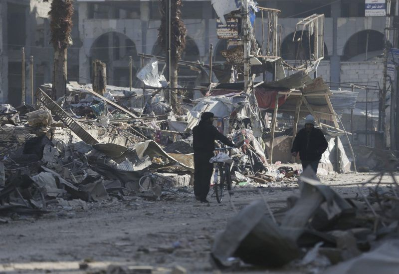 Men walk through a damaged area after what activists said were at least 20 air strikes by forces loyal to Syria's President Bashar al-Assad in the Douma neighbourhood of Damascus February 5, 2015. (Bassam Khabieh/Reuters)