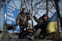 Ukrainian soldiers guard a road atop their military vehicle near Artemivsk, eastern Ukraine, Monday, Feb. 23, 2015. (Evgeniy Maloletka/AP)