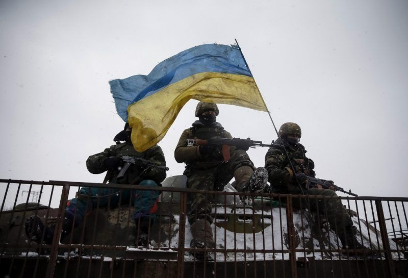 Members of the Ukrainian armed forces ride on a military vehicle near Debaltseve, eastern Ukraine, Feb. 16, 2015. REUTERS/Gleb Garanich