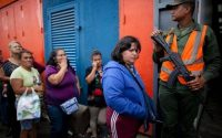 SHORTAGES: People line up outside the Dia a Dia supermarket in Caracas one day after the government took over the chain of stores to punish businesses it blames for worsening shortages. Ariana Cubillos AP