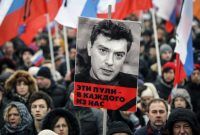 "A portrait of Kremlin critic Boris Nemtsov, who was shot dead on Friday night, is seen during a march to commemorate him in central Moscow March 1, 2015. The words under the portrait reads ""These bullets are meant for each of us."" REUTERS/Maxim Shemetov"