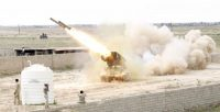 Iraqi security forces cover their ears as a rocket is launched during clashes with Islamic State militants at a frontline in Tikrit, March 28, 2015. REUTERS/Thaier Al-Sudani
